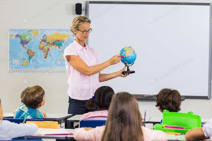 Lehrer mit Lektion mit einem Globus