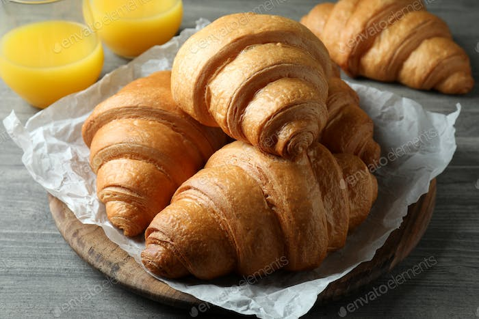 Tasty croissants and juice on gray textured table