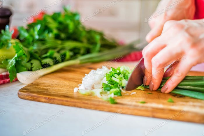 Female hand with knife cuts green leek in kitchen. Cooking vegetables