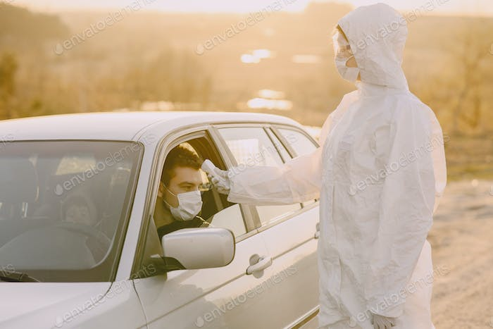 Person in a protective suit checks the temperature