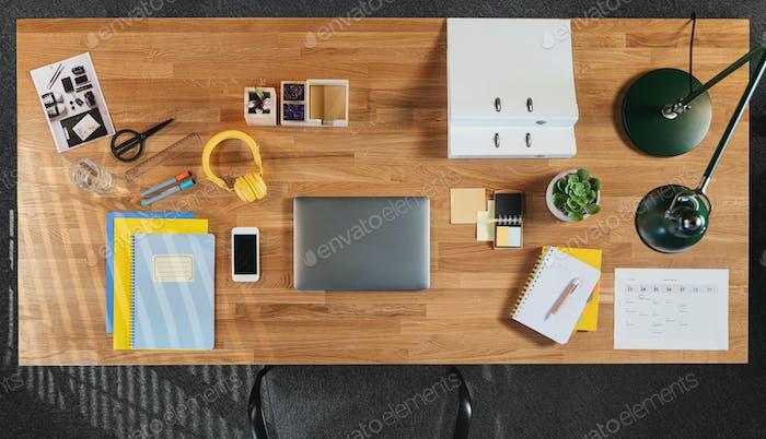 Draufsicht auf den Schreibtisch mit Computer, Tablet und Papierkram im Home-Office.