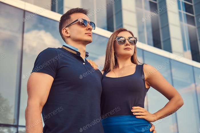 Attractive fashionable couple standing in the modern city against a skyscraper.