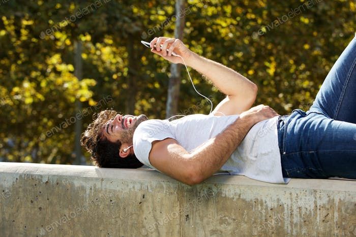 Happy man lying on wall in park with cellphone