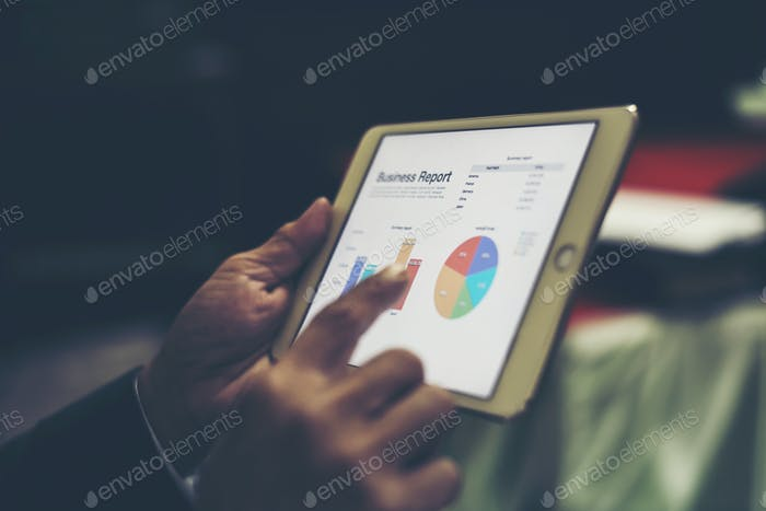 Business person hand holding financial statistics displayed on the tablet screen at office.