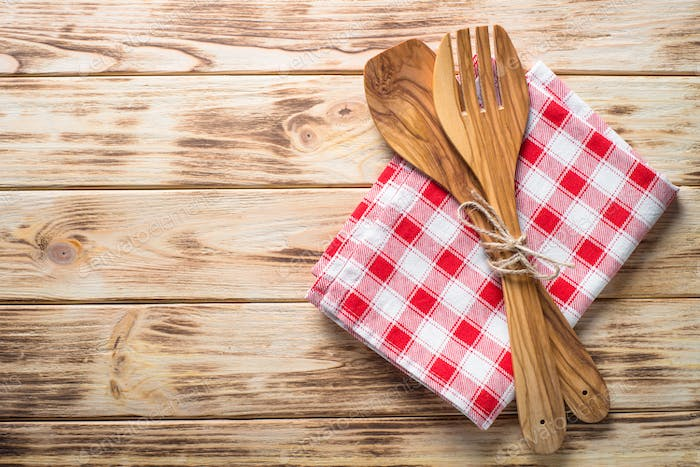 Kitchen table with utensil and tablecloth.