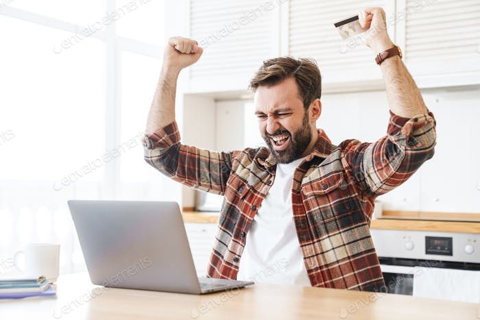 Portrait of excited man holding credit card and making winner gesture