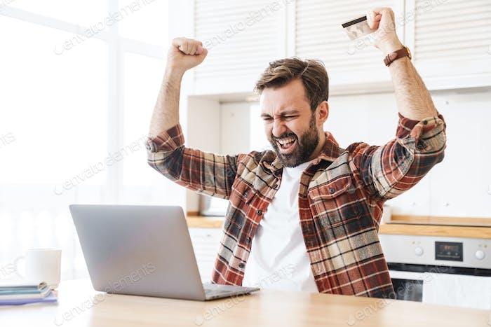 Портрет возбужденного человека, держащего кредитную карту и делающего жест победителя