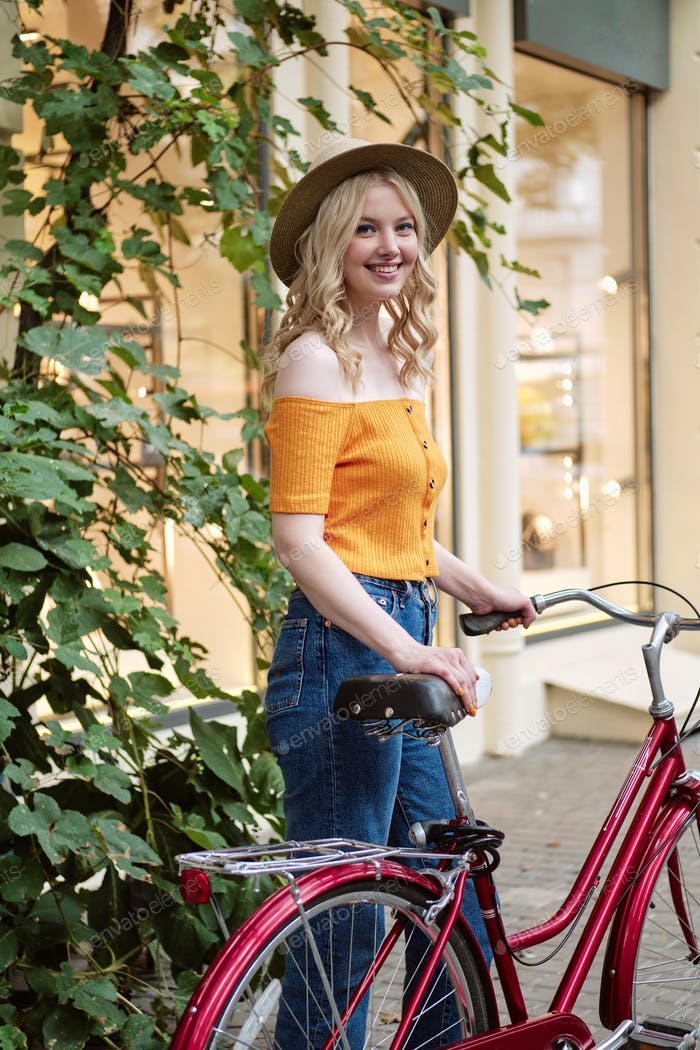 Romantic blond girl in hat happily looking in camera walking with classic bicycle on city street