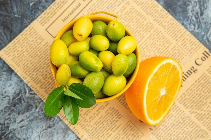Oben Nahaufnahme von Zitrusfrüchten in einem Korb auf Zeitung auf grauem Hintergrund