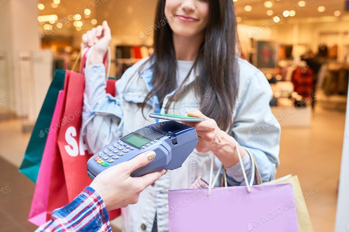 Shopaholic paying for clothing with  smartphone