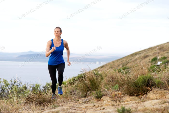 Woman running up hill with sea in background