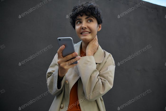 Meditative pretty dark haired curly woman with casual hairstyle holding smartphone