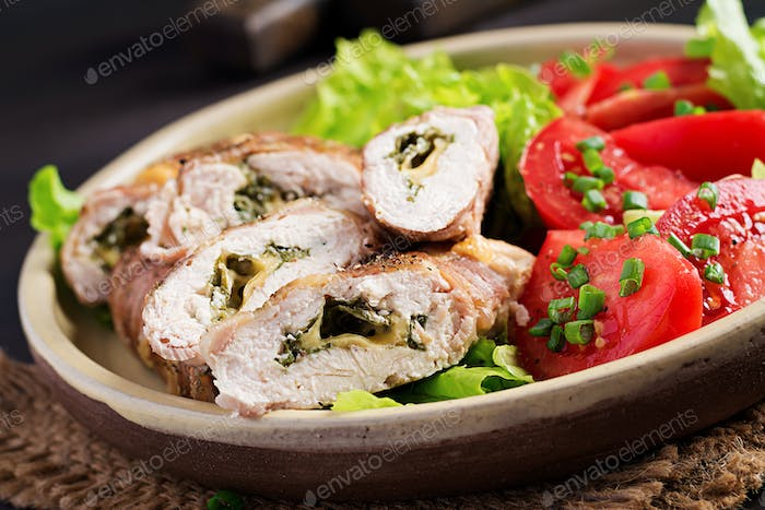 Delicious chicken rolls stuffed with cheese and spinach wrapped in strips of bacon.