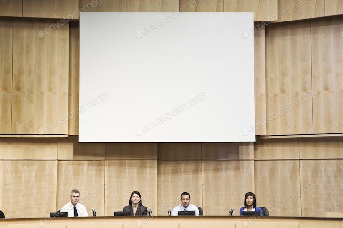 Eine Gruppe von Geschäftsfrauen und Männern in einem poltischen Treffen.