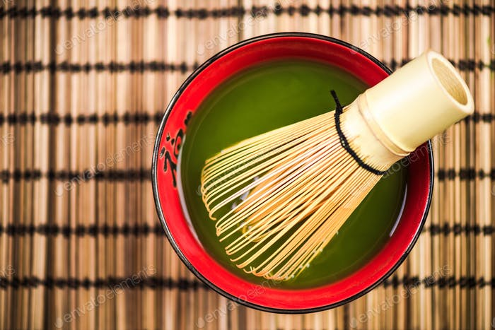 Preparation of Matcha green tea in bowl with whisk