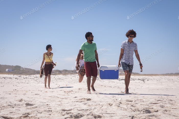 Group of friends carrying ice box and beer bottles while walking on the beach in the sunshine