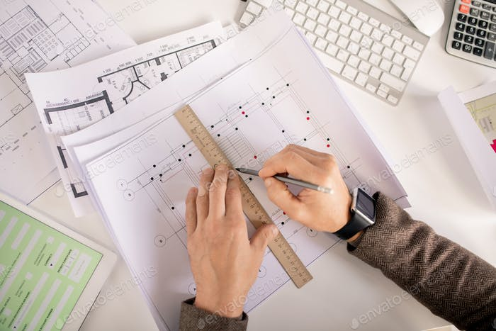 Overview of hands of engineer with pencil and ruler drawing line on sketch