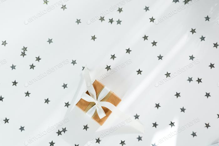present with white bow on white stars sparkling background. Festive backdrop for holidays: Birthday