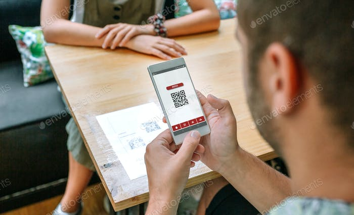 Man scanning restaurant menu QR code