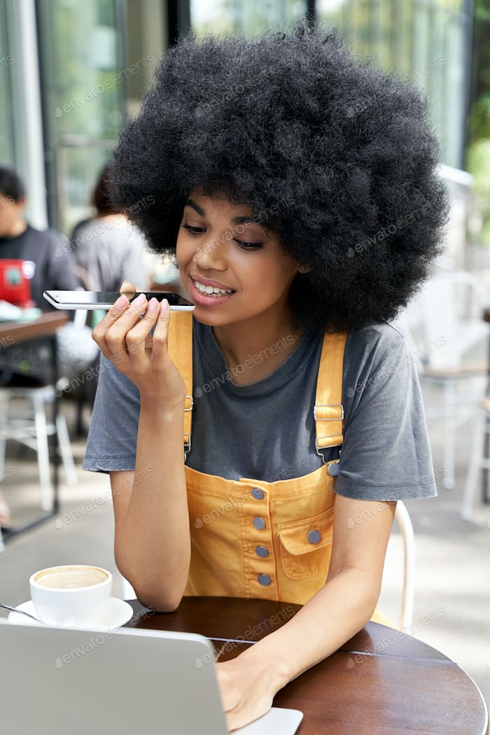 African woman using mobile voice recognition assistant sitting in outdoor cafe.