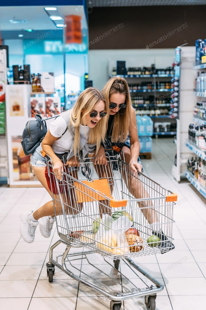 Two young girls have fun at the supermarket