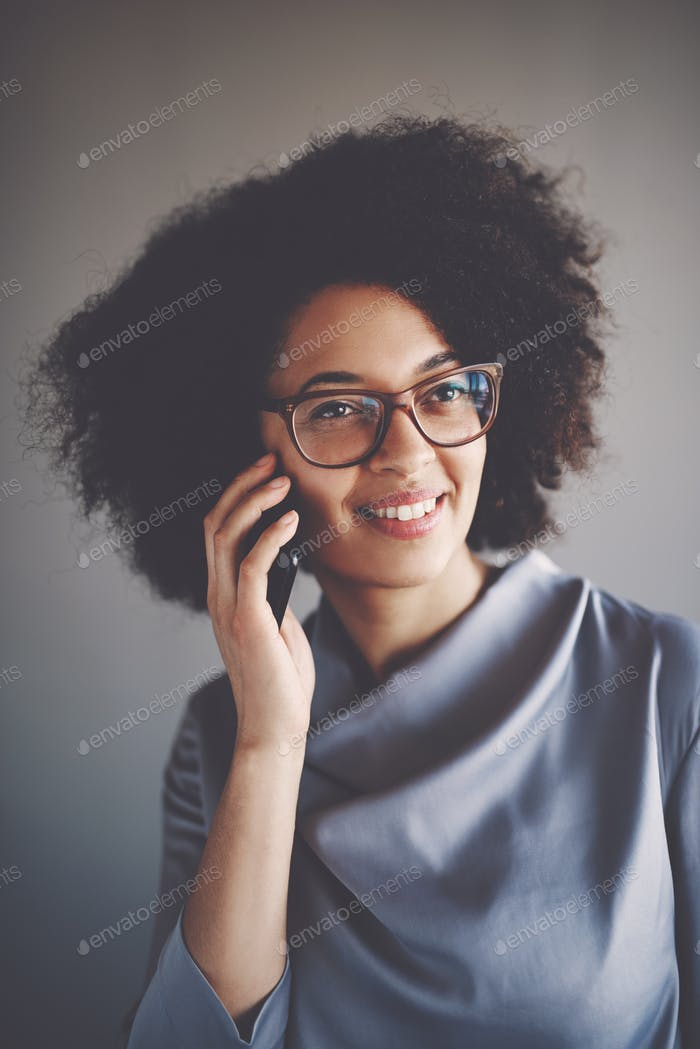 Smiling young African businesswoman talking on a cellphone