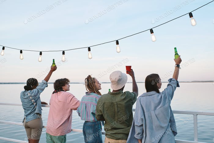 Row of young intercultural ecstatic friends having drinks on pier