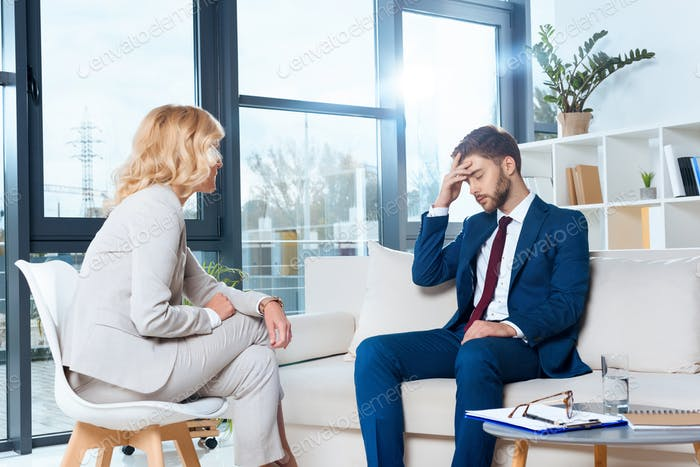 psychologist talking with depressed young patient at psychotherapy
