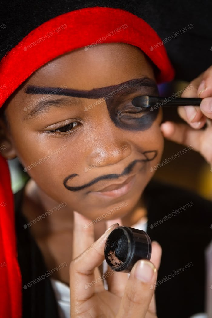 Hand of woman drawing on boy eyes