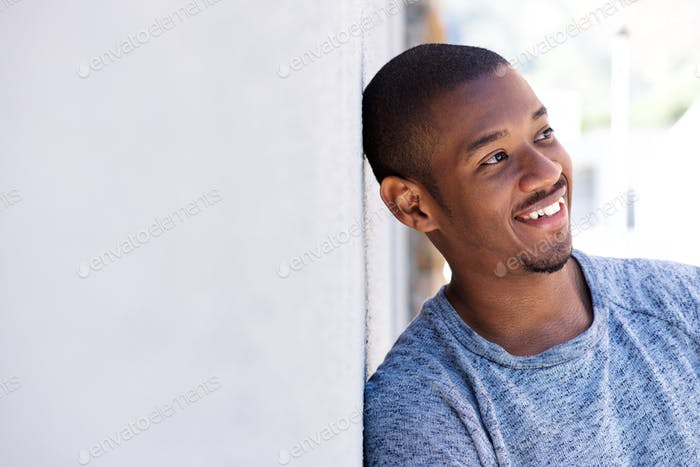 happy black guy leaning against wall
