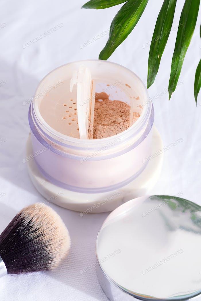Kunststoffbox mit Gesichtspuder und Pinsel für Make-up auf weißem Textilhintergrund mit grüner Handfläche