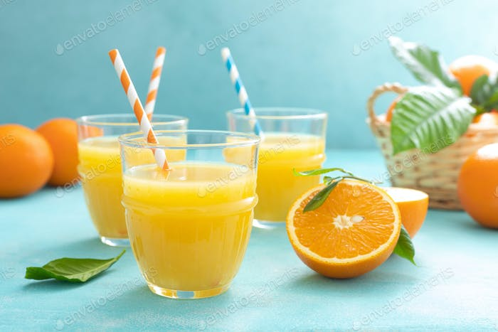 Orange freshly squeezed juice in glass and fresh fruits on a blue vivid background