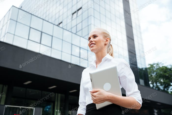 Businesswoman holding digital tablet while looking away against office building