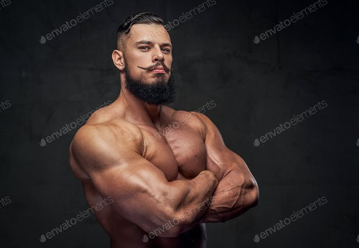 Bodybuilder with beard posing with crossed arms in studio