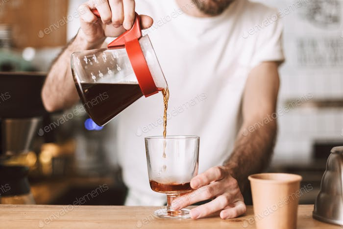 Close up photo of barista at bar counter pouring filter coffee in glass in cafe