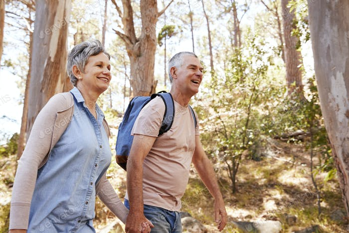Mature Couple Hiking Along Forest Path Together