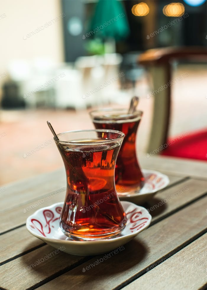 Turkish tea in traditional tulip glasses on table in street cafe