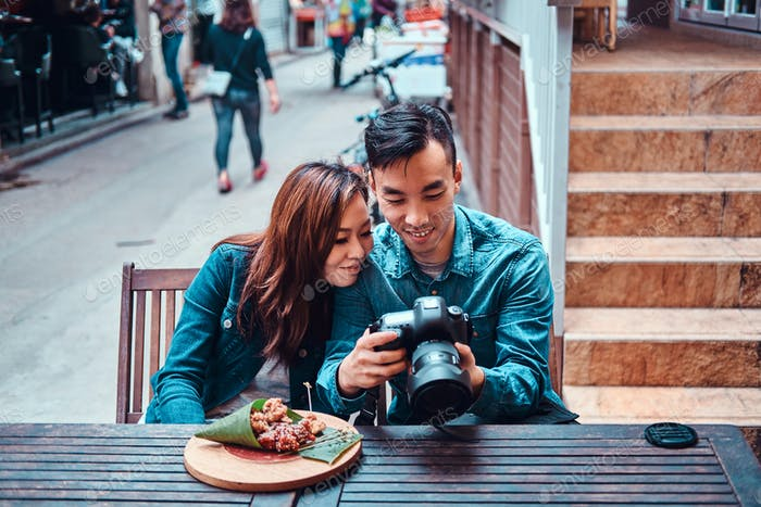 Asiatisches Paar genießen chinesisches Essen und Bilder ansehen