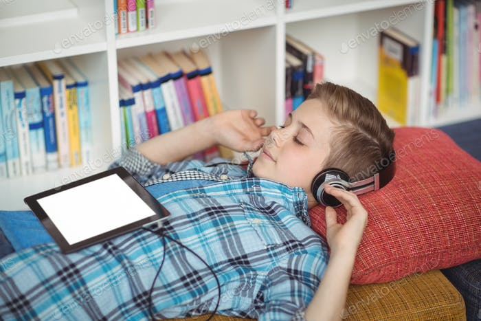 Schoolboy relaxing on couch while listening music on digital tablet in library