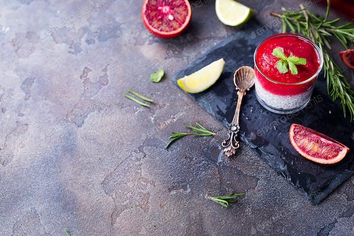 Chia Pudding mit frischen Beeren Püree und Honig mit Scheibe Zitrus auf Schiefer dunklen Hintergrund.