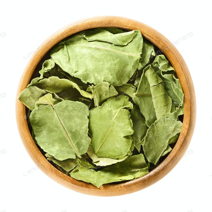 Dried kaffir lime leaves in wooden bowl over white