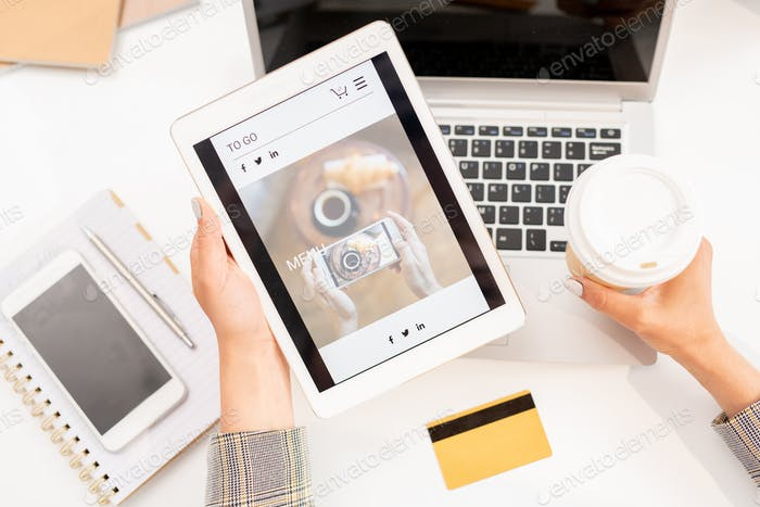 View of tablet with screensaver of online shop held by businesswoman