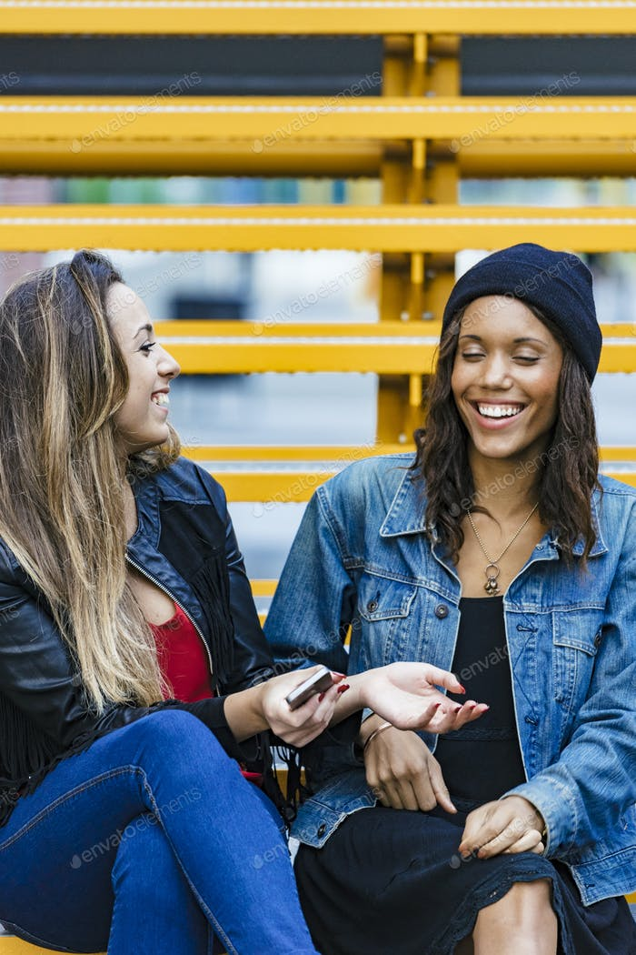 two mixed race female friends sitting and using a smartphone