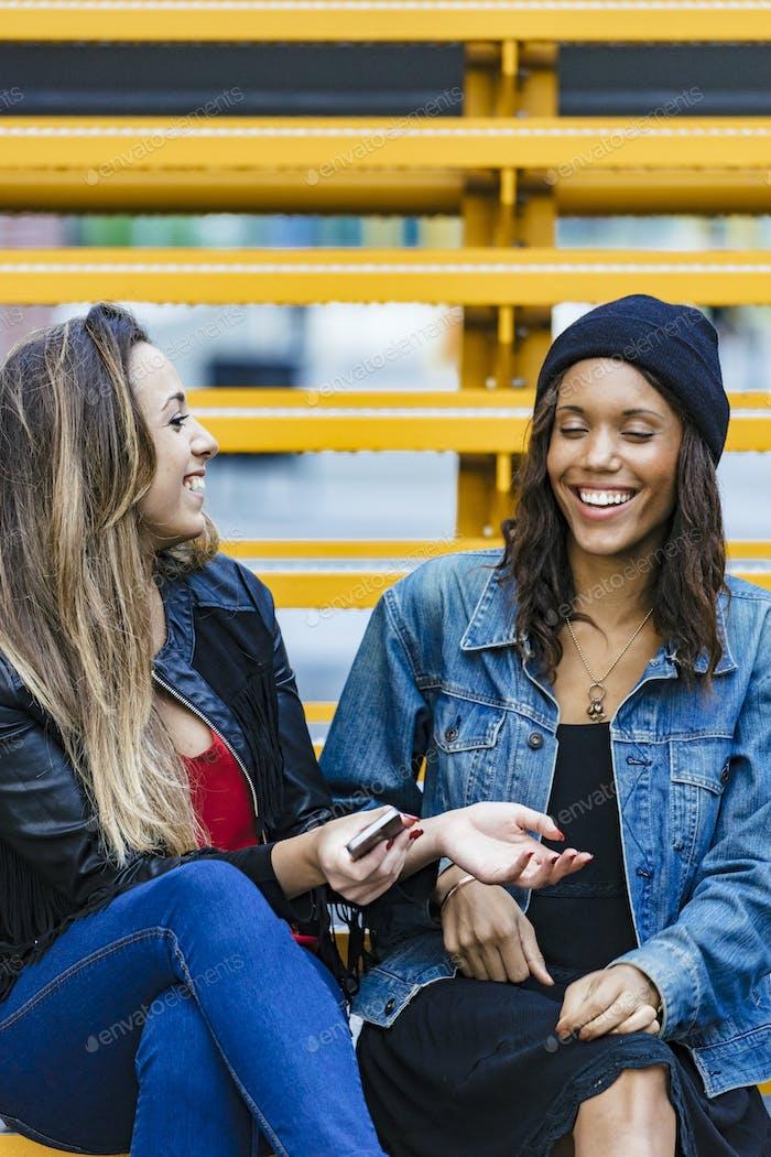 zwei gemischte Rennen weibliche Freunde sitzen und mit einem Smartphone