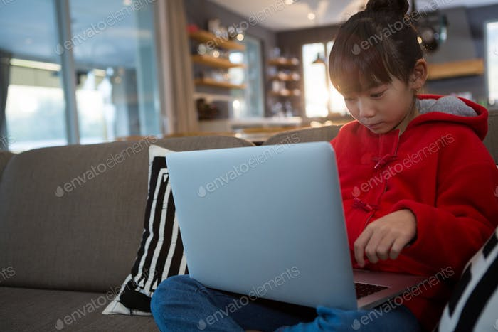 Relaxed girl using laptop on sofa