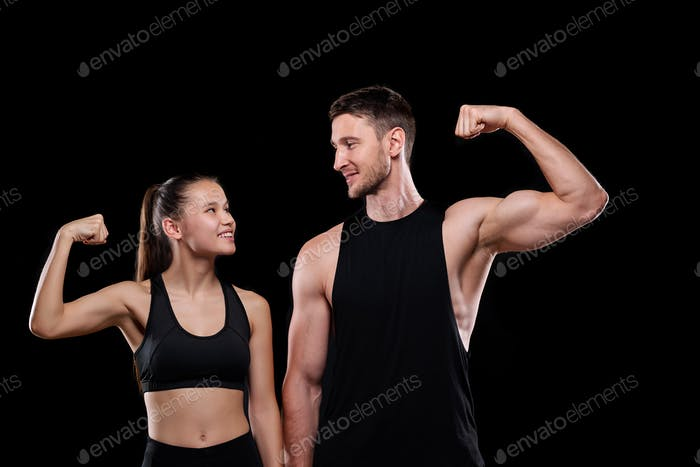 Young cheerful sports couple in activewear looking at each other