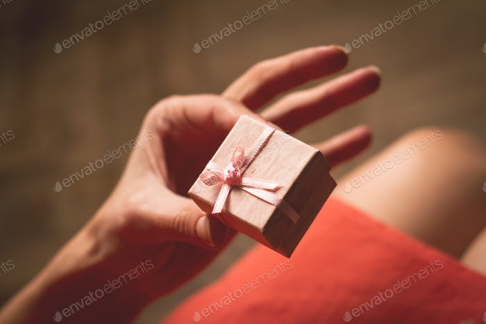 Woman holding in her hand a very small pink gift box above her k