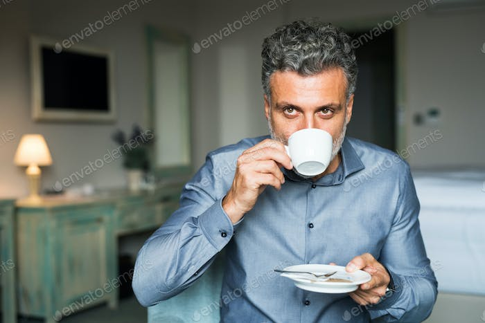 Mature businessman drinking coffee in a hotel room.
