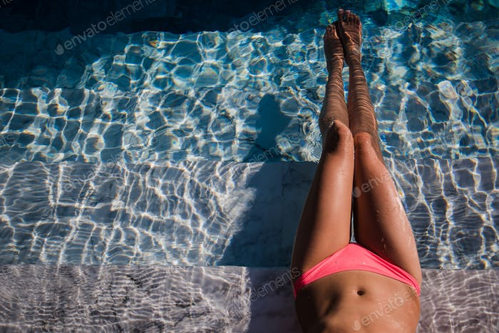 Female sexy tanned wet legs into water at pool.