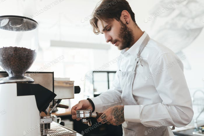 Barista in apron and white shirt making coffee by coffee machine in restaurant